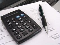 Calculadora y pluma con el balance Imágenes de archivo libres de regalías