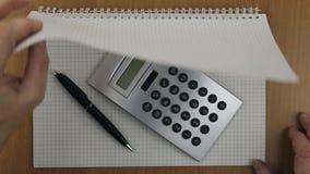 Calculadora y pluma en un cuaderno Dé vuelta a la hoja de la libreta al trabajo almacen de metraje de vídeo