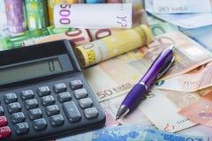 Calculadora y pluma en un fondo del dinero Imagenes de archivo