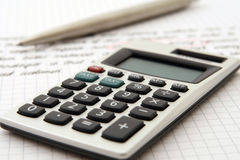 Calculadora y pluma que indican el trabajo/el estudio Imágenes de archivo libres de regalías