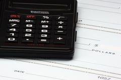 Calculadora y verificaciones Fotos de archivo