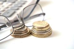 Calculadora y vidrios con las monedas Foto de archivo libre de regalías