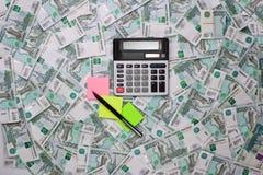 Calculadoras e etiquetas coloridas em um fundo do dinheiro Foto de Stock