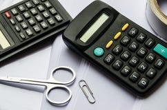 Calculadoras, escocés, tijeras y un clip en un fondo blanco imagenes de archivo