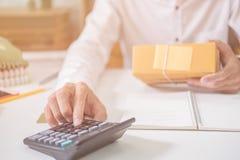 Calculando o custo do porte postal de um pacote pequeno Imagens de Stock