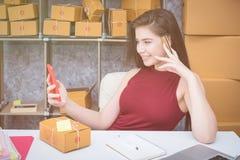 Calculando o custo do porte postal de um pacote pequeno, empresa pequena Fotografia de Stock Royalty Free