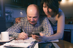 Calculate income and expenses in the family budget. Daughter helps her father count money and manage the family budget royalty free stock photos