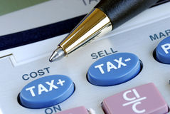 Calculate the tax. And the cost with a calculator Royalty Free Stock Photos