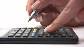 Calculating. Close-up shot of a person taking notes while using an old-fashioned calculator