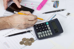Calculating accountant interrupted by his smart phone. While checking his sales data Stock Images