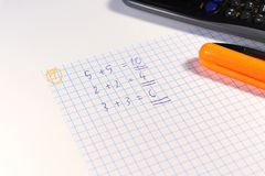 A calculating with calculator many difficult examples for math lesson before hour start. Orange felt tip pen and square paper royalty free stock images