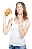 Calculating calories. Beautiful young woman holding hamburger Stock Images