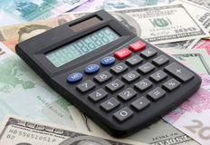 Calculating cash. Calculator on banknotes (euro, dollar, hrivna, rouble Royalty Free Stock Images