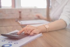 A business woman working on the laptop at home office. Calculating the cost of postage of a small package, Small business enterprise concerns for online Shopping Royalty Free Stock Photo