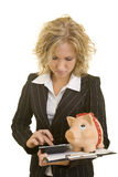 Calculating costs. Blonde business woman with calculator, a piggy bank and a clipboard royalty free stock photography
