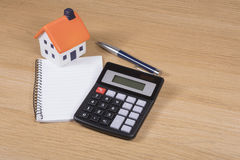 Calculating the costs of home improvements. Or purchase in a conceptual image with a model toy house, calculator, notebook and pen on a wooden table royalty free stock photo