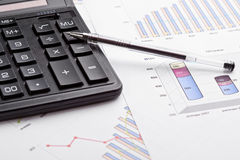 Calculating finances. Calculator and pen on business graphics royalty free stock image