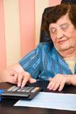 calculating gammalare kvinna för affär Arkivbilder