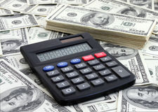 Calculating income. Calculator near a pile of dollars Stock Photography