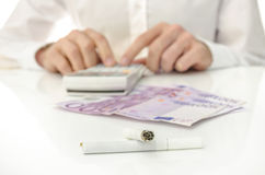 Calculating monthly costs of cigarette addiction Royalty Free Stock Photo