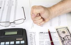 Calculating numbers for income tax return with pen, glasses and calculator. stock images