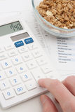Calculating daily nutrition intake. Healthy eating concept - man calculate his daily nutrition intake. Muesli in glass bowl, calculator, calendar and nutrition Royalty Free Stock Photography