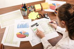 Calculating on the office desk Royalty Free Stock Images
