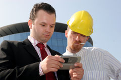 Calculating a profit. Young businessman showing something on a cell phone(PDA), to a construction worker in front of a corporate building Royalty Free Stock Images