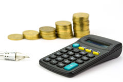 Calculating progress of savings. Calculator, pen and stack of gold coins over white background Stock Photography