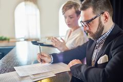 Calculating Restaurant Profit. Profile view of confident bearded restaurant manager standing at counter and calculating profit, pretty waitress standing next to Royalty Free Stock Photo