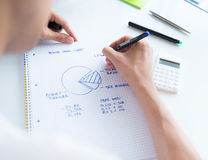 Calculating sales earnings. Person sitting at the desk, calculating sales earnings and drawing circular diagram with numbers royalty free stock photography