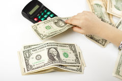 Calculating the savings. Hand separating dollars by type on white background and a black calculator Stock Image