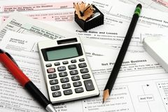 Calculating Taxes. Calculator tax forms pen pencil eraser shapener stock images