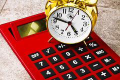 Calculating Time. The calculator is next to the alarm clock. The idea is it's to represent calculating time or time calculations Royalty Free Stock Photography