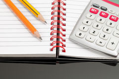 Calculation. Close up Image of a Notebook, Two Pencils and a Calculator on a Desktop with Black Glass Stock Photography