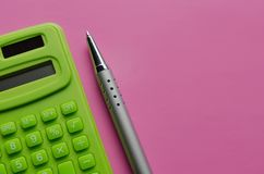 The calculation of the budget, taxes and the cost of the calculator on a pink background. Top view of calculator with pen royalty free stock image