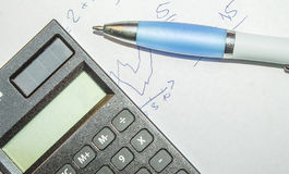Calculation. Calculator and pen on paper Royalty Free Stock Photography