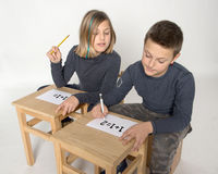Calculation problem. Children intent on solving a problem of calculation Stock Photo