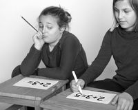 Calculation problem. Children intent on solving a problem of calculation Stock Photos
