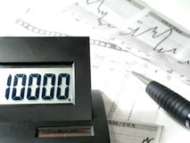 Calculation of profit and loss. Calculator on top of some stock papers.  Shallow depth of field. Focus on the calculator.  Light play in the back.  Main subject Stock Photography