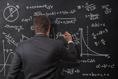 Calculations on the board. Businessman making calculations on the blackboard royalty free stock photo