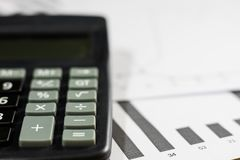 Calculations, calculations and economics on paper. Calculator an. D charts on a wooden table Royalty Free Stock Photos