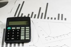 Calculations, calculations and economics on paper. Calculator an. D charts on a wooden table Royalty Free Stock Images