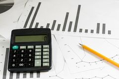 Calculations, calculations and economics on paper. Calculator an. D charts on a wooden table Stock Images