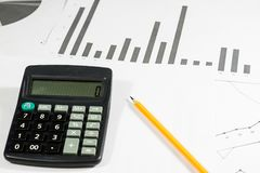 Calculations, calculations and economics on paper. Calculator an. D charts on a wooden table Stock Image