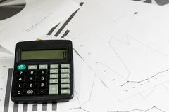 Calculations, calculations and economics on paper. Calculator an. D charts on a wooden table Royalty Free Stock Photo