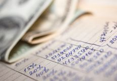 Calculations and 100-dollar bills. Hand-written calculations and 100-dollar bills. Bookkeeping accounting. Economy. Money savings and budget. Bank deposits royalty free stock photography