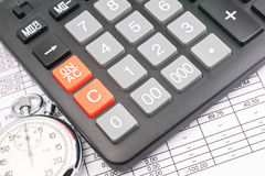 Calculator. Closeup of an income statement with a calculator and stopwatch Royalty Free Stock Photos