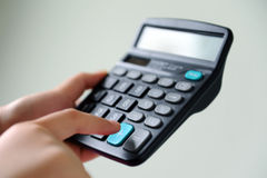 Calculator. A hand pushing a 'plus' button on a calculator Stock Images
