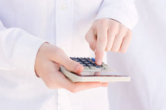 Calculator. Finger pressing key on white calculator Stock Photos